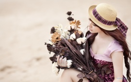 Korean brunette with a hat and holding a dry bouquet